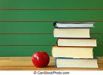 Stack of books and red apple on desk.