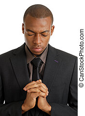 Business man praying with eyes closed - This is an image of...