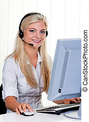 Woman at computer with headset and Hotline - Young woman...