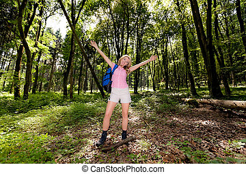 Woman in nature while hiking. His arms in the air