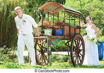 Bride and groom - Funny bride and groom with cart outdoor