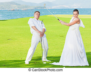 Wedding golf - Bride and groom are playing golf at wedding...
