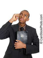 Man holding a bible whilst thinking
