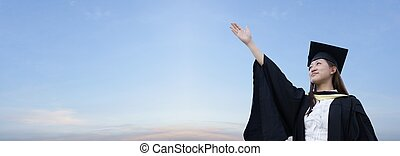 Aspiring asian lady graduate raising hand with panoramic sky