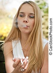 Young woman smoking cigarette outdoors