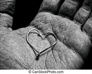 Fisherman love - Shape or symbol of a heart in hand of an...