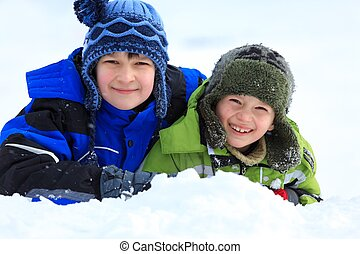 Children playing in snow - Smiling young children playing in...