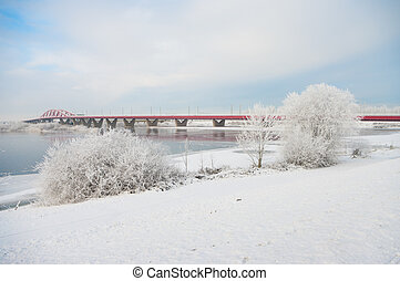 railway bridge across river in a snowy white landscape