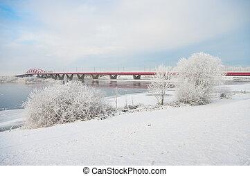 railway bridge across river in a snowy white landscape