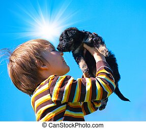 Boy and puppy - Happy boy holding a black puppy