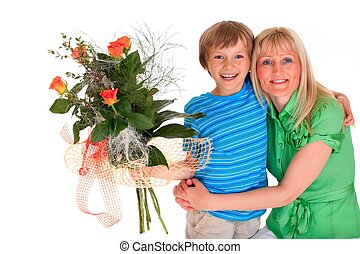 Boy giving mother flowers - Close up of smiling young boy...