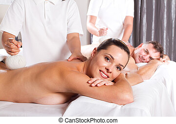 couple having back massage - happy man and woman having Thai...