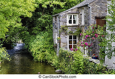 Old English cottage on river - An old, quaint English...