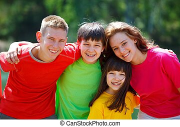 Children Outdoors - Smiling teenagers with younger brother...