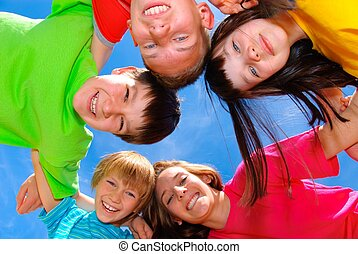 Smiling children wearing bright colored shirts standing in a...