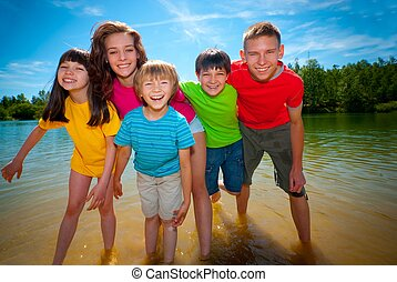 Children in lake - Children in colorful clothes playing...