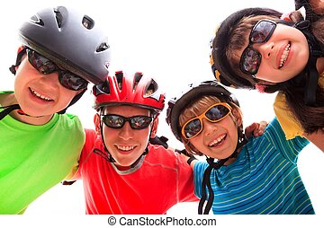 Kids with helmets and pads - Four kids wearing helmets and...