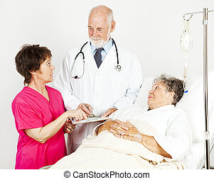 Discussing Patient Progress - Nurse and doctor discussing a...