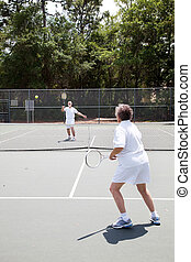 Senior Tennis Match - Senior man and woman playing in a...