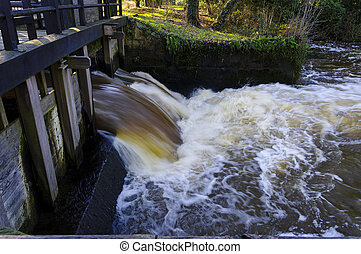 open sluice - flowing water coming outside an old sluice