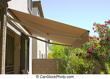 Awning above back yard door to residential two-storied house...
