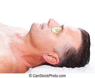 man with cucumber facial