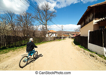 Boy riding a bike on rural road