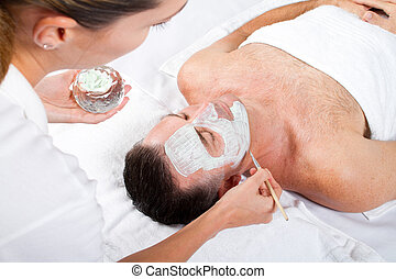 middle aged man facial mask in luxury beauty spa