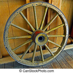 Old Wagon Wheel - An Old Wagon Wheel rests inside of a rural...