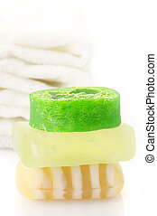 Soap and towels - Stack of various soaps and white towels on...