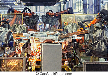 robots in a car factory - robots welding in a car factory