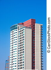 Red and White Condo Tower in Blue Sky