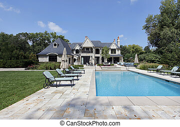 Swimming pool with large deck outside of luxury home