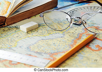 map and glasses - opened old atlas book on map and glasses...