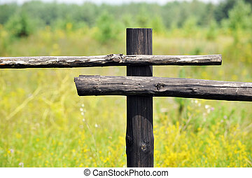 View on  fence in  middle of field with  forest in distance