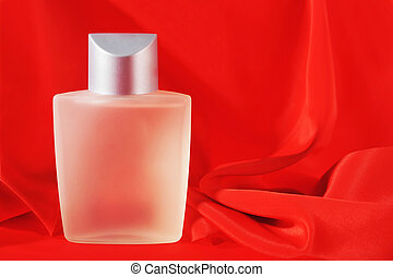 Bottle of perfume, isolated on red close up