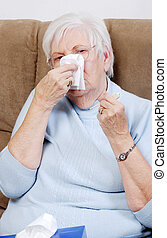 closeup sick senior woman blowing her nose