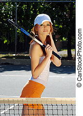 young woman playing tennis with orange skirt