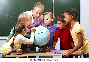 Explanation - Portrait of pupils looking at globe while...