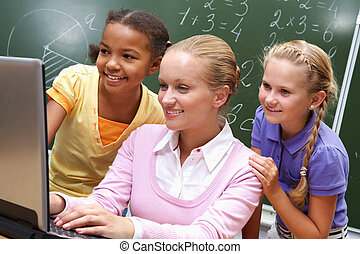 Working together - Portrait of two girls and teacher looking...