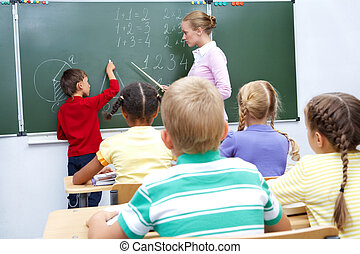 By the blackboard - Photo of elementary student by...