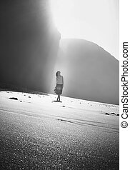 Young girl walking under arch rock formation near Atlantic...