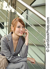 Young business manager woman holding cellphone and sitting,...