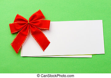 Red bow with card isolated on green