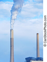 Smokestacks of power station on sky background
