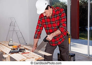 Construction Worker Using Hand Saw - A construction worker...