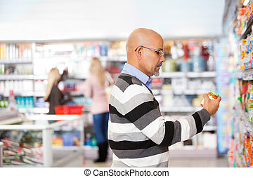 Mature man shopping in the supermarket with people in the...