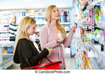 Product Comparison - Young women shopping together in the...