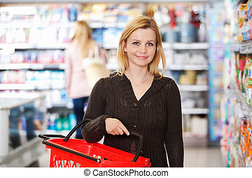 Grocery Store Portrait - Portrait of a young woman carrying...