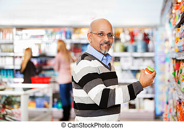 Smiling mature man shopping in the supermarket with people...